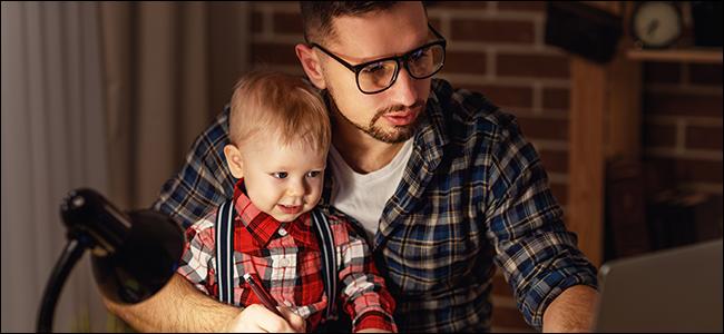 Ein Vater und ein Kind lesen etwas von einem Laptop