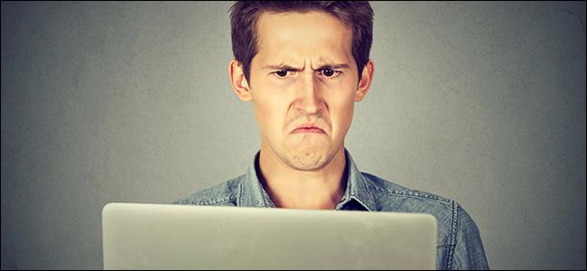 Ein Mann starrt angewidert auf seinen Laptop.  Offensichtlich sieht der Film, mit dem er prahlte, wie ein Dreckbündel aus.