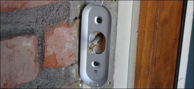 Eine Nest Hello-Halterung, die mit durchsteckenden Drähten an einem Türrahmen befestigt ist.