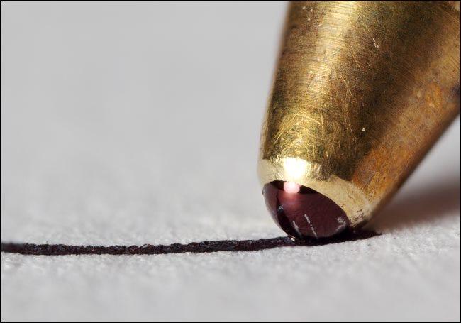 Ein Makrofoto der Spitze eines Kugelschreibers, der auf ein Stück Papier schreibt.