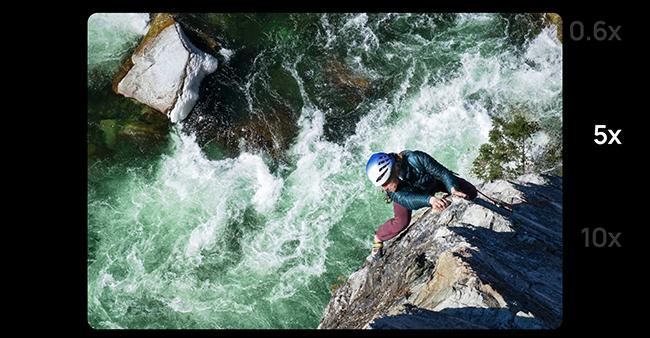 Zoomaufnahme eines Mannes an einem Seil, der die Felsen neben einem rauschenden Fluss erklimmt.