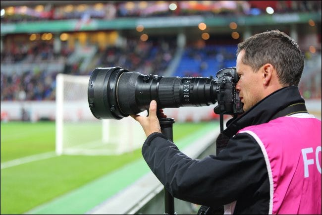 Ein Fotograf mit einem großen optischen Zoomobjektiv bei einem Fußballspiel.