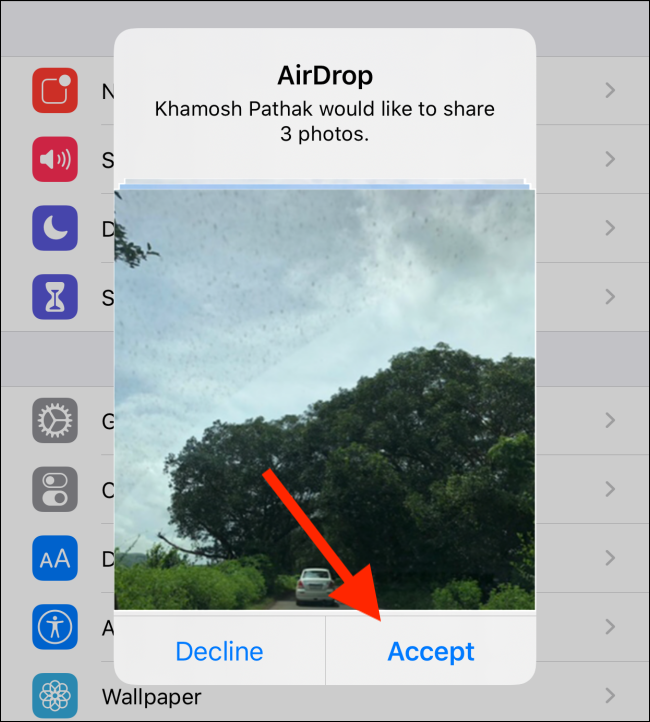 """Eine AirDrop-Anfrage zum Teilen von Fotos;  Ihr Kontakt muss tippen """"Akzeptieren"""" um die Dateiübertragung zu starten."""