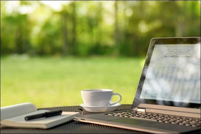 Laptop und Kaffee auf einem Tisch im Freien