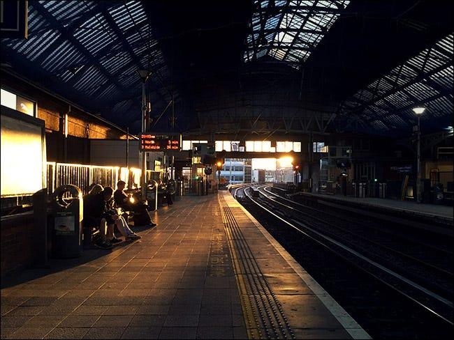 Innenraum des Bahnhofs mit Sonnenuntergang im Hintergrund