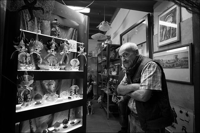 Älterer Mann mit verschränkten Armen im Kuriositätengeschäft