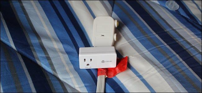 Ein iClever Smart Plug über einem Stecker einer Klimaanlage über einer blauen Decke.