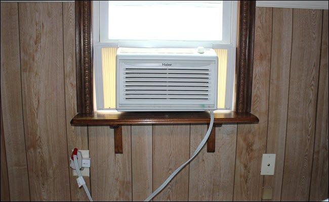Eine Fenster-Klimaanlage, die an einen Smart Plug angeschlossen ist, der an eine Steckdose angeschlossen ist.