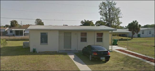 Ein sehr kleines Haus mit drei Fenstern, ohne zweite Etage und einem Carport.