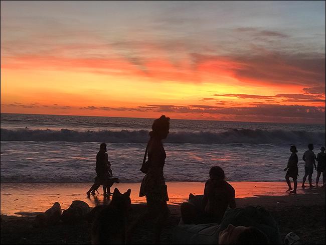 Schattenbilder der Leute, die am Strand bei Sonnenuntergang gehen.