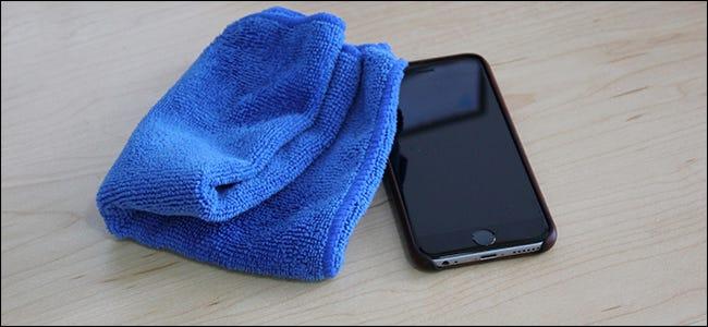 Ein blaues Mikrofasertuch, das neben einem iPhone sitzt.