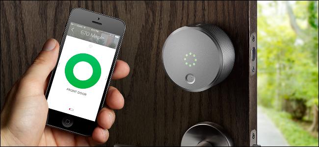 Die Hand eines Mannes hält ein iPhone, das die August Smart Lock-App zeigt, und öffnet eine Tür mit einem August Smart Lock.