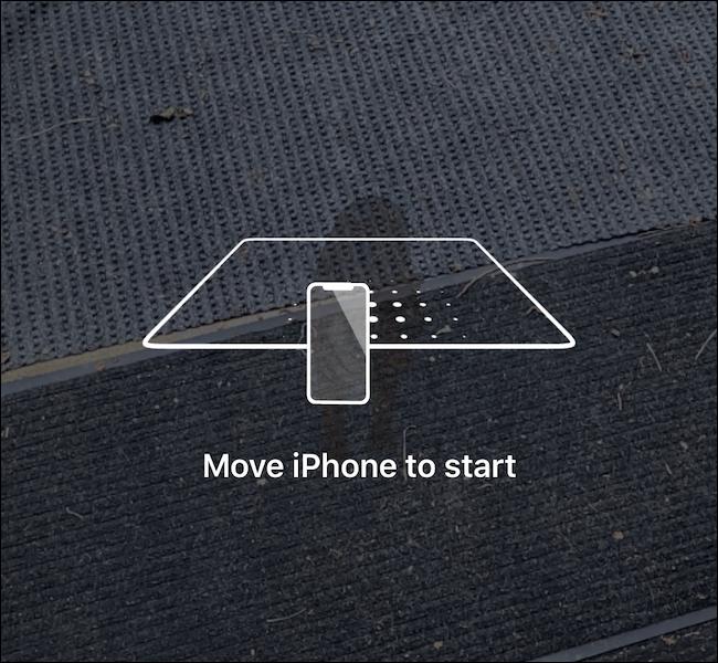 Ein Telefon, das den Boden scannt, um das AR-Erlebnis zu laden.