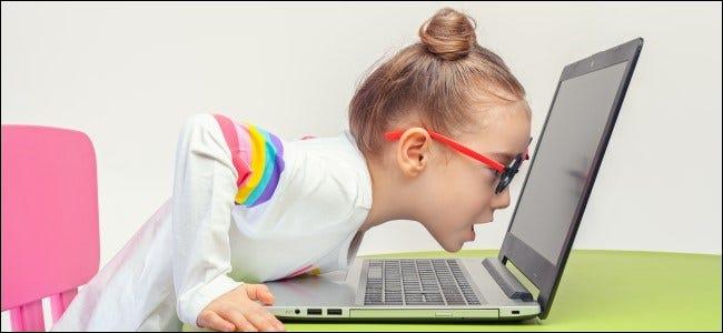 Kind mit Brille lehnt an Laptop