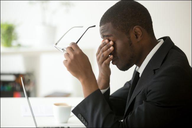 Ein Mann sitzt vor seinem Laptop, hält seine Brille und reibt sich die Augen.