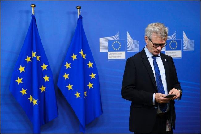 Ein Mann mit einem Smartphone mit zwei EU-Flaggen im Rücken.