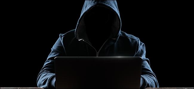 Vermummter Hacker am Laptop