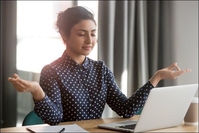 Eine Frau meditiert in einem Büro vor einem MacBook.