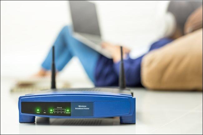 Ein WLAN-Router mit einem Kind, das im Hintergrund einen Laptop verwendet.