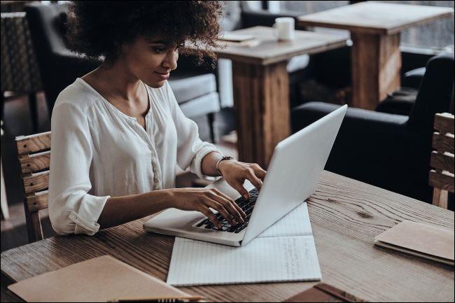 Eine lächelnde Frau, die auf einem Laptopcomputer schreibt.