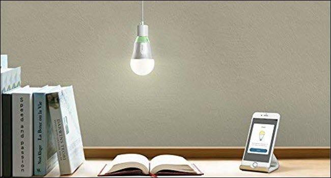 Eine TP-Link-WLAN-Glühbirne hängt über einem offenen Buch und einem Handy auf einem Schreibtisch.