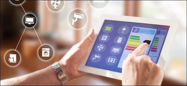 Die Hände eines Mannes, der ein Tablet verwendet, um Smarthome-Geräte in einer App zu steuern.
